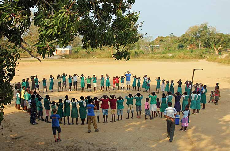 Volunteer outside in a very large circle of children palying Simon Says