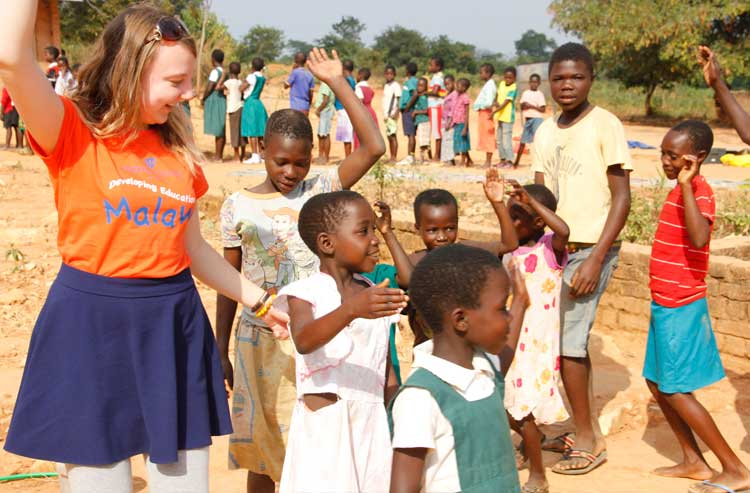 A volunteer playing outside with Malawi school children