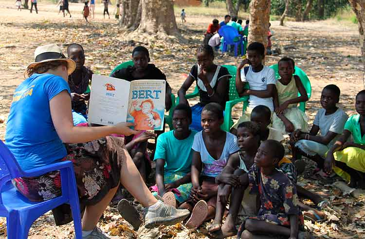 A volunteer reading to a group of young Malawi children