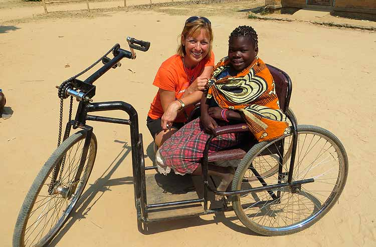 Volunteer smilingwith a disabled Malawi school girl