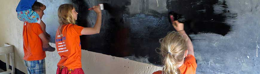 Young volunteers repainting old, tired classroom blackboards in Malawi